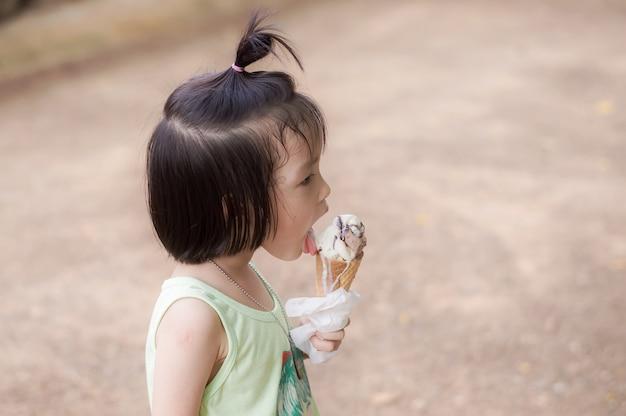 Cute girl enjoy eating a melting chocolate ice-cream