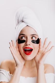 귀여운 소녀는 아침 피부 관리 절차를 즐기고 흰 벽에 눈 아래 패치로 포즈를 취합니다.