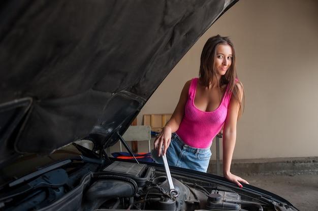 Cute girl examining car engine at the auto repair shop