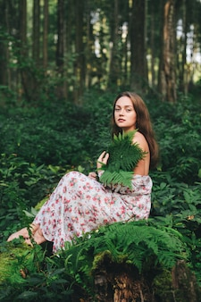 A cute girl in a floral dress is sitting with a fern bouquet in the forest.