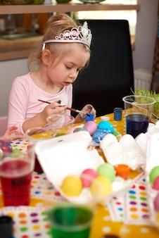 Милая девушка сосредоточилась на своих пасхальных яйцах ручной работы