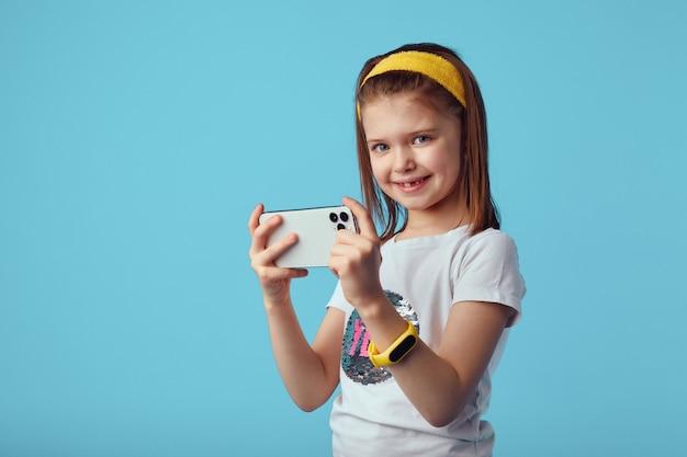Симпатичная девушка-геймер играет в онлайн-игры, развлекая их с помощью потрясающего приложения