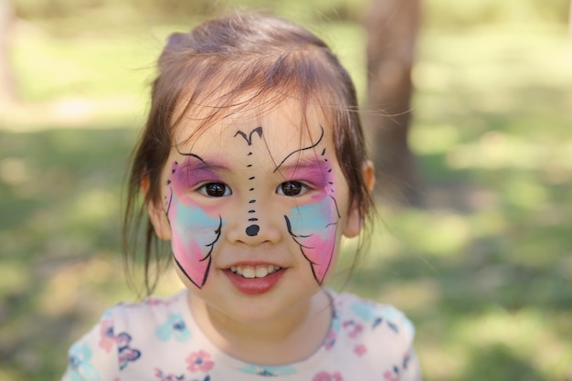 Cute girl getting face painted as a butterfly