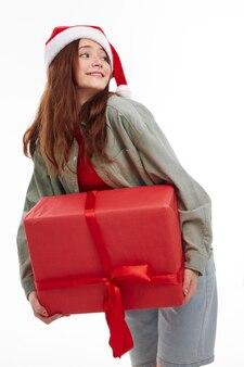 Милая девушка подарочная красная коробка новогодние забавы светлом фоне. фото высокого качества