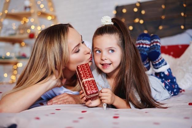 彼女のお母さんにクリスマスプレゼントを与えるかわいい女の子