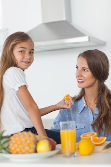Cute girl giving an orange segment to her mother