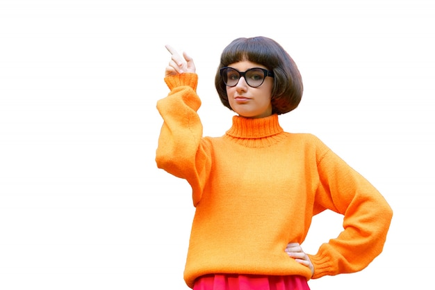 A cute girl in glasses and a bright orange sweater points her finger to the side on a white background.