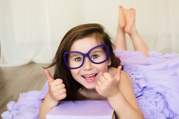 Cute girl in the glasses holding a purple book