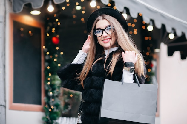 Cute girl in glasses walks the christmas streets of the city doing new year's shopping