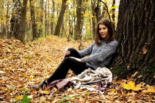 Cute girl in a gray jacket sitting in the autumn forest on a yellow leaf near a large tree