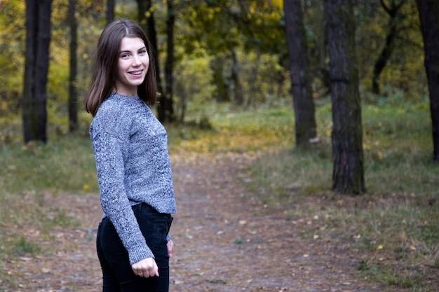 Cute girl in a gray sweater is half a turn on the road in the autumn forest.