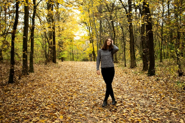 Cute girl in a gray sweater with braces on her teeth stands on the road in the autumn forest