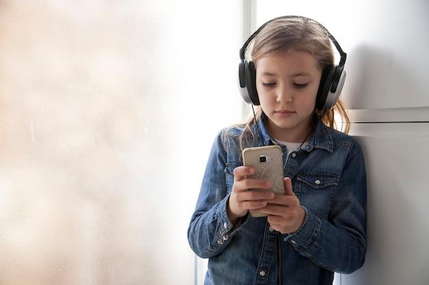 Cute girl in headphones using smartphone