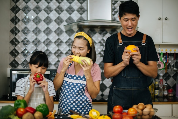 Cute girl help her parents are cutting vegetables and smiling while cooking together in kitchen
