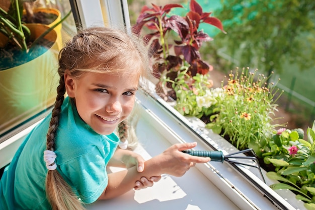 Cute girl helping to care for home plants on the balcony window plant parents concept