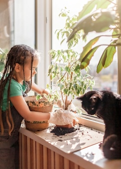 Cute girl helping to care for home plants on the balcony window