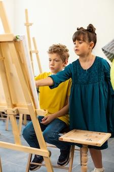 Милая девочка помогает своему однокласснику рисовать в художественной школе
