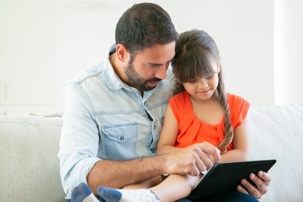 Cute girl and her dad watching movie or reading on tablet screen together.