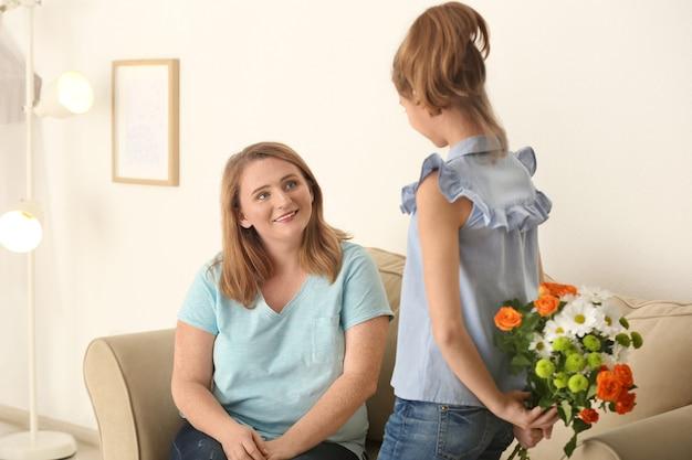 그녀의 뒤에 어머니를 위해 꽃을 숨기고 귀여운 소녀