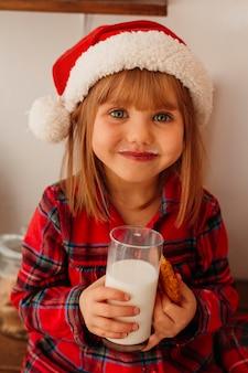 クリスマスのクッキーと牛乳のガラスを保持しているかわいい女の子