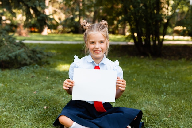 흰색 시트를 들고 귀여운 소녀입니다. 흰 종이와 금발 소녀입니다. 작은 여 학생 빈 시트를 들고 있다.