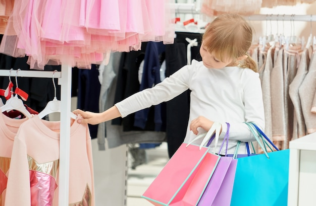 Cute girl holding bags and choosing pink sweater in store