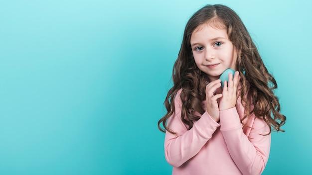 Cute girl holding blue easter egg