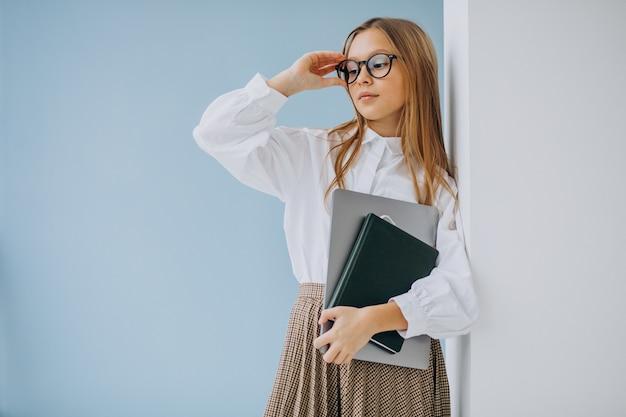 Милая девушка держит книгу и ноутбук в офисе