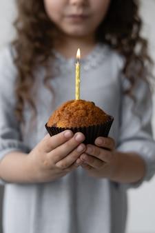Cute girl holding a celebratory cupcake.