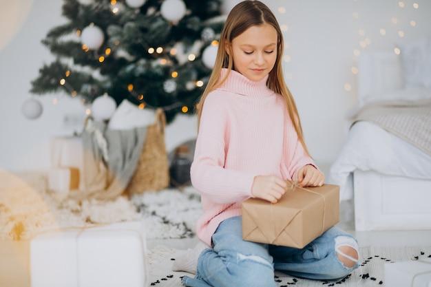 クリスマスツリーでクリスマスプレゼントを持っているかわいい女の子