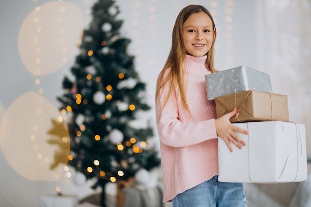 Cute girl holding christmas presents by christmas tree