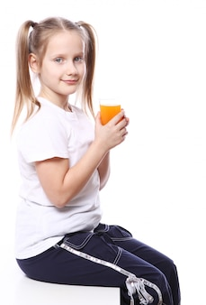 Cute girl holding glass of fresh orange juice