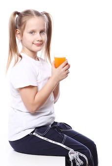 Милая девушка держит стакан свежего апельсинового сока