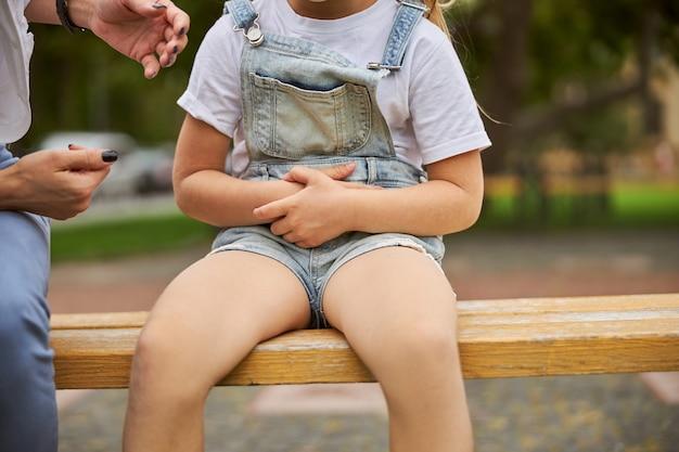 공원에서 벤치에 앉아있는 동안 배꼽에 손을 잡고 귀여운 소녀