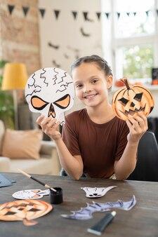 Cute girl holding handmade paper skull and pumpkin
