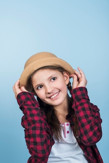 Cute girl holding hat on head