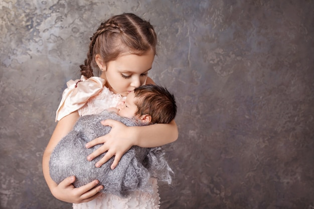 Cute girl holding her little brother. happy sister kissing her newborn baby brother. copyspace
