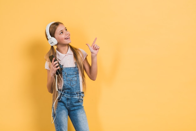 Cute girl holding mobile in hand listening music through headphone pointing finger upward against yellow backdrop