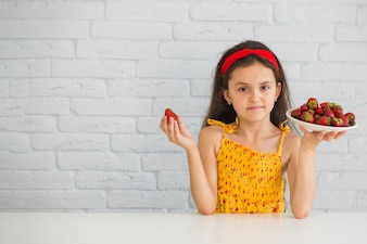 Cute girl holding plate of red strawberries against white brick wall