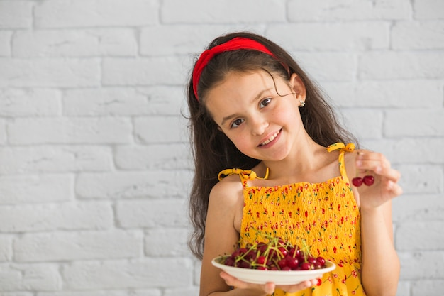 Cute girl holding plate of red cherries against white brick wall