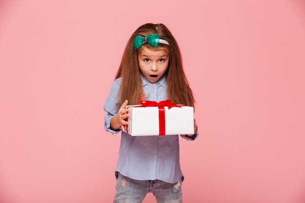 Cute girl holding present box with open mouth being excited and surprised to get birthday gift