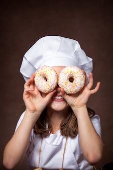 2つのおいしいドーナツを手に持ったかわいい女の子。楽しいポーズ、シェフの帽子で遊ぶ