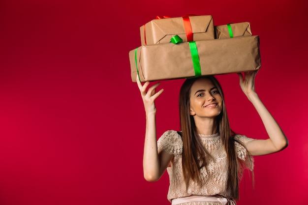 Милая девушка держит подарки на голове и улыбается на красном фоне с пустым пространством