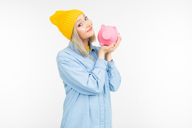 Милая девушка в голубой рубашке с банком для экономии денег на белом фоне с копией пространства.