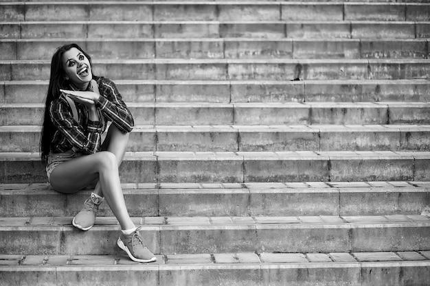 Симпатичная девушка в макияже клоуна на фоне черно-белого фото