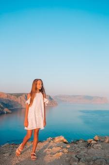 Милая девушка в платье на горе, потрясающие скалы и море на закате. красивая природа