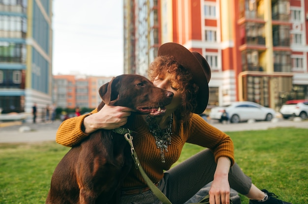 Милая девушка в шляпе сидит на лужайке с коричневой собакой