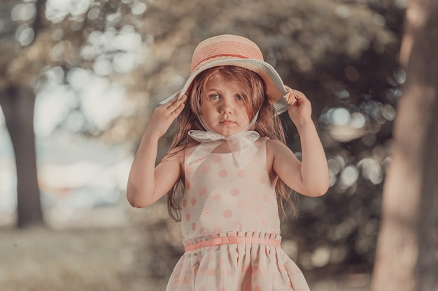 Милая девушка в розовом платье с шляпой стоит в парке летом. фото высокого качества