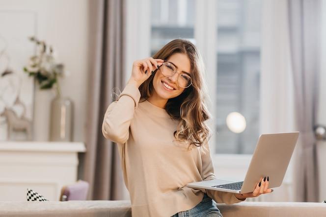 Милая девушка в бежевой рубашке трогает очки и держит ноутбук с улыбкой