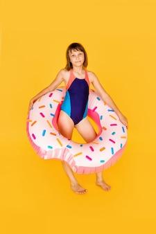 노란색에 거대한 nflated 고무 링과 파란색 수영복에 귀여운 소녀
